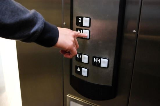 FINGER PUSHING AN ELEVATOR BUTTON